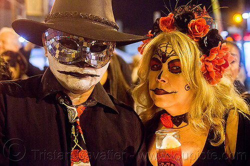 man with black mosaic mask and hat - dia de los muertos (san francisco), black hat, carnival mask, couple, day of the dead, dia de los muertos, face painting, facepaint, flame, flower headdress, flowers, glass candle, halloween, man, mosaic mask, night, red, skull makeup, woman