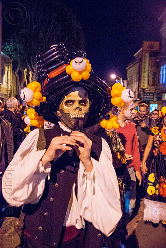 man with skull mask playing flute - dia de los muertos, balloon hat, day of the dead, dia de los muertos, halloween, man, night, party balloons, playing flute, playing music, skull mask