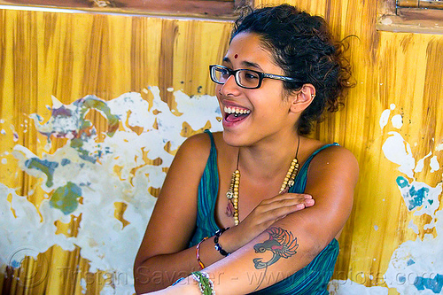 maryam and peeling paint wall, arm tattoo, bindi, bird tattoo, bracelets, djembe drum, drummer, eyeglasses, eyewear, india, maryam, musical instrument, necklaces, peeling paint, percussion, phoenix tattoo, prescription glasses, rishikesh, sitting, spectacles, tattoos, tongue piercing, woman