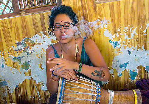 maryam smoking a joint, arm tattoo, bindi, bird tattoo, bracelets, cigarette, djembe drum, drummer, eyeglasses, eyewear, ganja, india, joint, maryam, musical instrument, necklaces, peeling paint, percussion, phoenix tattoo, prescription glasses, rishikesh, sitting, smoke, smoking, spectacles, tattoos, weed, woman