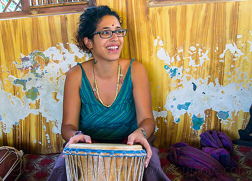 maryam with djembe drum, bracelets, drummer, eyeglasses, eyewear, musical instrument, necklaces, peeling paint, people, percussion, prescription glasses, rishikesh, sitting, spectacles, tilaka, wall, woman