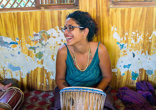maryam with djembe drum, bindi, bracelets, djembe drum, drummer, eyeglasses, eyewear, maryam, musical instrument, necklaces, peeling paint, percussion, prescription glasses, rishikesh, sitting, spectacles, wall, woman