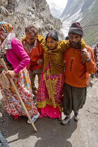 men helping exhausted woman on trail - amarnath yatra (pilgrimage) - kashmir, amarnath yatra, exhausted, hiking, hindu pilgrimage, india, kashmir, men, mountain trail, mountains, pilgrims, saree, sari, trekking, woman