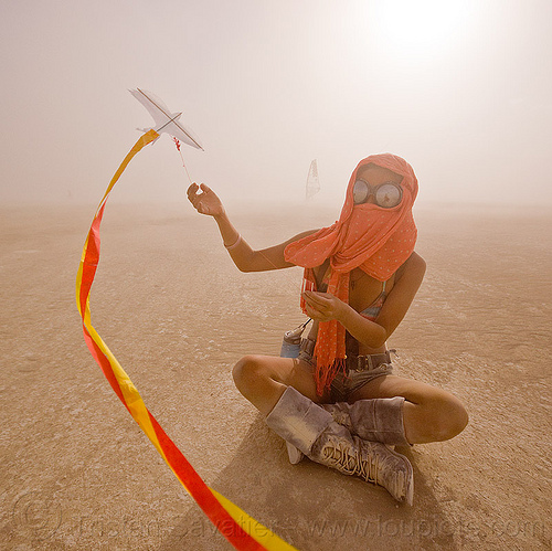 mini kite, boots, burning man, cross-legged, dust storm, flying, goggles, haboob, minah, mini kite, orange scarf, playa dust, red, sitting, streamers, string, whiteout, wind, woman, yellow