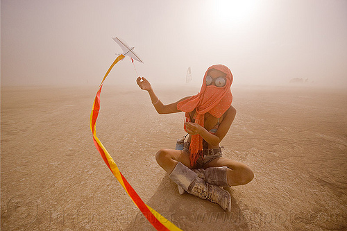 mini-kite, boots, burning man, cross-legged, dust storm, flying, goggles, haboob, minah, mini kite, orange scarf, playa dust, red, sitting, streamers, string, whiteout, wind, woman, yellow