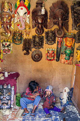 mother and her little girl sitting in souvenir shop (nepal), bhaktapur, child, daughter, ganesha, hanging, kid, little girl, masks, mother, sitting, wall, wood carving