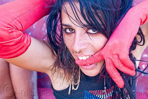 mumu mariane charline - woman biting her finger - red gloves, burning man, lip piercing, makeup, nose piercing, septum piercing, woman