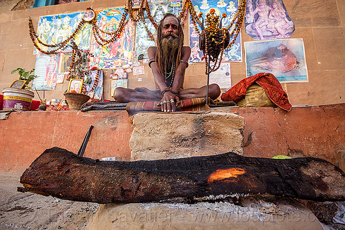 naga sadhu (india), baba, beard, campfire, damaru drum, dreadlocks, dreads, ghats, hindu, hinduism, man, posters, ritual drum, sadhu, sitting, tree log, varanasi, wall, wood