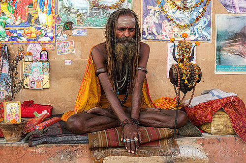 naga sadhu (india), baba, beard, bracelets, cross-legged, damaru drum, dreadlocks, finger rings, ghats, hindu ritual drum, hinduism, india, man, necklaces, posters, sadhu, sitting, tilak, trident, varanasi