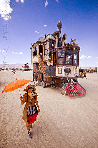 the neverwas haul art car - burning man 2012, art car, burning man, mutant vehicles, neverwas, orange umbrella, steampunk, victorian, walking, woman