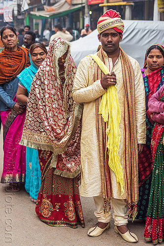 newlyweds - indian wedding - groom holding bride in tow like a trophy, couple, dressed-up, headdress, headwear, man, people, standing, street, traditional, turban, varanasi, women