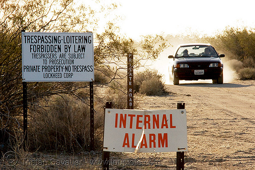 no trespassing!, car, desert, dirt road, forbidden, interbal alarm, lockheed corp, loitering, no trespassing, private property, private road, signs, unpaved