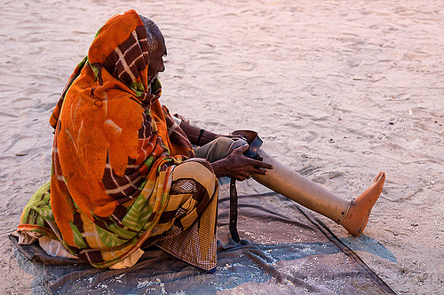 old man adjusting his prosthetic leg (india), amputated, bhagwa, hindu pilgrimage, hinduism, india, leg amputee, maha kumbh mela, man, prosthetic leg, prosthetics, saffron color, sitting
