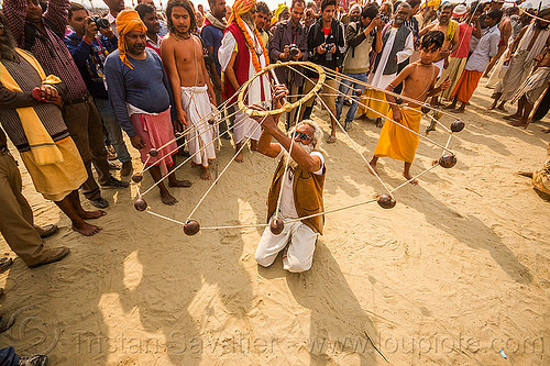 old man spinning balls with ropes (india), crowd, game, hindu pilgrimage, hinduism, india, indian spinning balls, maha kumbh mela, man, metal balls, performer, ropes, spectators