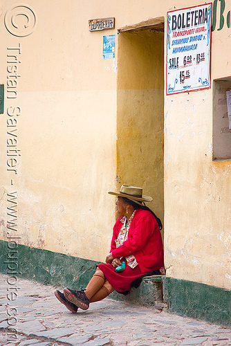 old woman waiting for the bus (argentina), boleteria, cobblestones, door, doorway, hat, house, indigenous, iruya, noroeste argentino, porch, quebrada de humahuaca, quechua, red, sitting, wall, woman