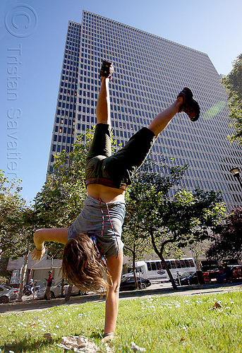 one hand cartwheeling, cartwheeling, catrwheel, city park, gymnastics, hirise building, jessika, lawn, one hand, single handed, trees, upside-down, woman