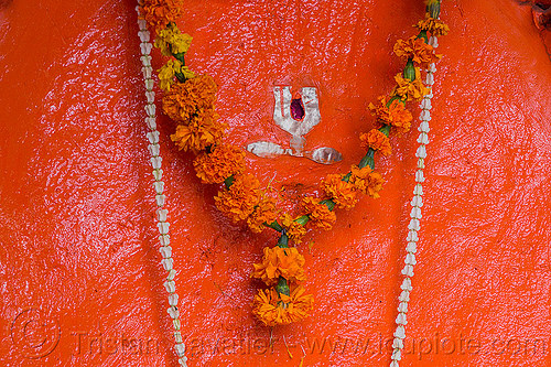 painted stone representing shiva (india), flowers, hinduism, marigold, necklaces, orange, rishikesh, shiva, shrine, symbol, tilak, tilaka