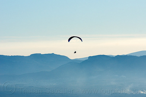 paragliding - paraglider flying in hazy sky, backlight, flying, freedom, haze, hazy, horizon, lonely, paraglider, paragliding, peaceful, silhouette