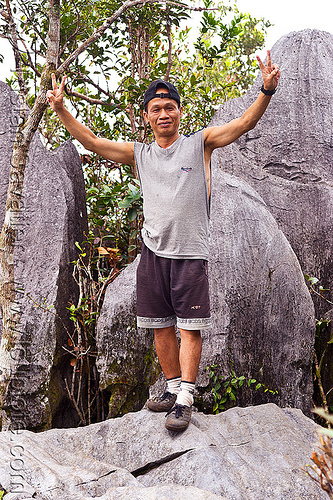 park guide ipoi lawin at the mulu pinnacles summit (borneo), erosion, geology, guide, gunung mulu national park, ipoi, jungle, karst, karstic, limestone, man, peace sign, pinnacles, rain forest, rocks, standng, stone, v-sign