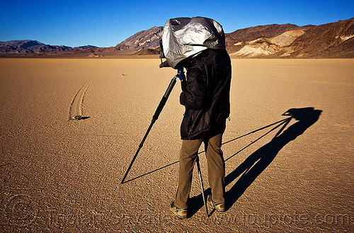 photographing a sailing stone on the racetrack - death valley, cracked mud, death valley, desert, dry lake, dry mud, film camera, hood, large format, man, mountains, moving rock, photographer, photographic chamber, racetrack playa, sailing stone, shadow, sliding rock, track, tripod
