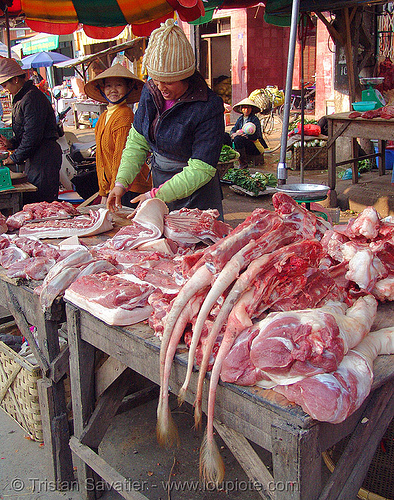 pig tails on sale! - vietnam, asian woman, butcher, lang sơn, market, meat, meat market, meat shop, people, pork, raw, raw meat, stall, street market