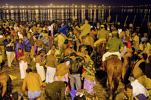 police horses patrolling the crowd of hindu pilgrims gathering at kumbh mela 2013 (india), cops, crowd control, fence, ganga river, ganges river, hindu, hinduism, holy bath, holy dip, horse riding, horseback riding, kumbha mela, law enforcement, maha kumbh mela, men, mounted police, night, paush purnima, pilgrims, police horses, police officers, reflections, ritual bath, river bank, river bath, river bathing, street lights, triveni sangam, water, women, yatris