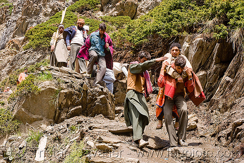 porters carrying exhausted woman on trail - amarnath yatra (pilgrimage) - kashmir, amarnath yatra, kashmir, men, mountain trail, mountains, pilgrimage, pilgrims, porters, trekking, wallahs, woman, yatris, अमरनाथ गुफा