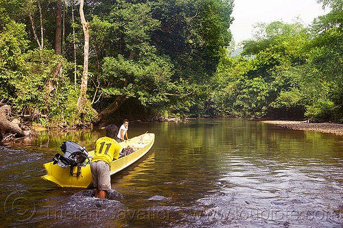 pushing a boat in the shallow waters of sungai melinau river - mulu (borneo), boatman, boatmen, borneo, gunung mulu national park, jungle, malaysia, melinau river, men, plants, rain forest, river bed, river boat, rocks, shallow river, small boat, sungai melinau, trees