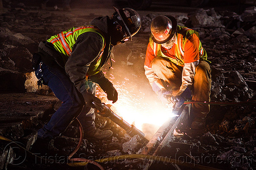 railroad workers cutting a track rail with a oxy-acetylene torch, dust mask, high-visibility jacket, high-visibility vest, light rail, man, muni, night, ntk, oxy-acetylene cutting torch, oxy-fuel cutting, railroad construction, railroad tracks, rails, railway tracks, reflective jacket, reflective vest, safety glasses, safety gloves, safety helmet, safety vest, san francisco municipal railway, sparks, track maintenance, track work, welder, worker, working