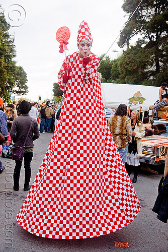 red and white stiltwalker with giant lollipop, checkered, clown, costume, giant lollipop, jesster, red lollipop, stilts, stiltwalker, stiltwalking, white, woman
