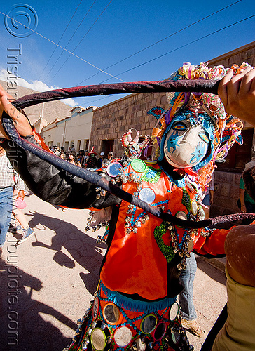 red diablo carnavalero holding tail - carnaval  - tilcara (argentina), andean carnival, confettis, costume, diablo carnavalero, diablo de carnaval, folklore, horns, indigenous culture, man, mask, mirrors, noroeste argentino, quebrada de humahuaca, quechua culture, serpentine throws, tilcara, tribal