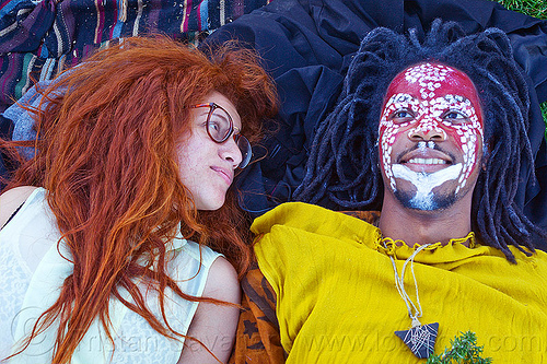 redhead & dreadlocks - couple in dolores park (san francisco), african american man, african face paint, black man, curly hair, dreadlocks, eyeglasses, eyewear, face painting, facepaint, glasses, jason, long hair, lulu, lying down, makeup, red, redhead, spectacles, stone necklace, triangular necklace, tribal face paint, white, woman, yellow tunic