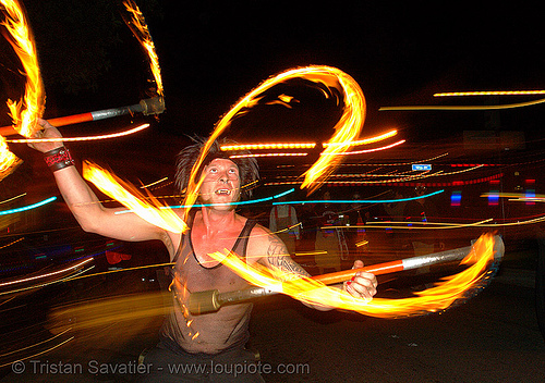 ro spinning fire staffs in the street, double staff, fire dancer, fire dancing, fire performer, fire spinning, fire staves, flames, long exposure, march of light, night, people, pyronauts