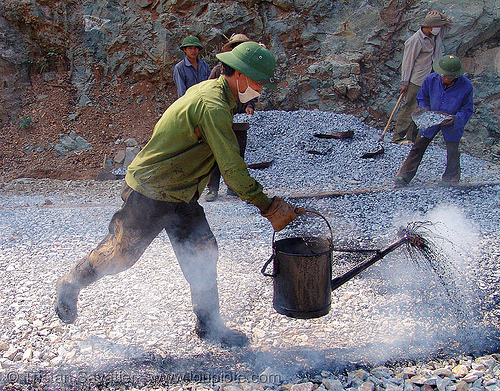 road paving - spraying hot asphalt over gravel with watering can - vietnam, gravel, groundwork, hot asphalt, hot bitumen, macadam, men, pavement, paving, people, petroleum, road construction, roadworks, smoke, smoking, spraying, watering can, workers, working