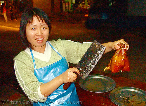 roasted piglet head - should I cut it for you? - vietnam, asian woman, cooked, food, lang sơn, market, meat, merchant, night, pig head, pork, roasted pig, roasted piglet, vendor