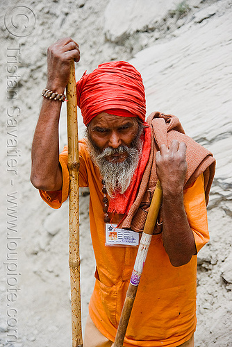 sadhu (hindu holy man) - amarnath yatra (pilgrimage) resting on trail - kashmir, amarnath yatra, baba, beard, bhagwa, hiking cane, hindu holy man, hindu pilgrimage, hinduism, india, kashmir, mountain trail, mountains, old man, pilgrim, resting, sadhu, saffron color, trekking, walking stick
