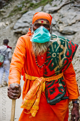 sadhu (hindu holy man) with dust mask on trail - amarnath yatra (pilgrimage) - kashmir, amarnath yatra, baba, beard, bhagwa, dust mask, hiking, hindu holy man, hindu pilgrimage, hinduism, india, kashmir, mountain trail, mountains, old man, pilgrim, sadhu, saffron color, surgical mask, tilak, trekking