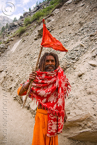 sadhu (hindu holy man) with red flag on trail - amarnath yatra (pilgrimage) - kashmir, amarnath yatra, baba, beard, hindu holy man, hinduism, kashmir, mountain trail, mountains, old man, pilgrim, pilgrimage, sadhu, trekking, yatris, अमरनाथ गुफा
