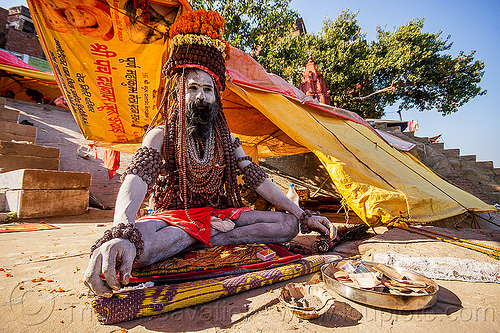 sadhu sitting crossed-legged on the ghats of varanasi (india), baba, bank-notes, beard, cross-legged, hindu, hinduism, holy ash, man, money, offerings, people, rudraksha, rudraksha beads, sacred ash, tarps, vibhuti, yellow