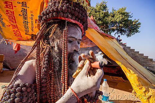 sadhu smoking chillum of weed on the ghats of varanasi (india), baba, beard, chillum, ganja, ghats, hindu, hinduism, india, man, pipe, rudraksha beads, sadhu, smoke, smoking, tarps, varanasi, weed, yellow