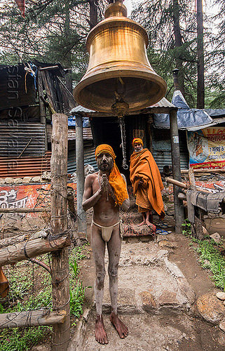 sadhu under large brass bell (india), baba, bell, bhagirathi valley, bhagwa, brass, hinduism, holy ash, india, men, naga babas, naga sadhus, sacred ash, sadhu, saffron color, standing, test1, vibhuti