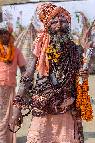 sadhu with ritual rudraksha beads necklaces - kumbh mela (india), baba, beard, cellphone, headdress, hindu pilgrimage, hinduism, india, maha kumbh mela, man, marigold flowers, mobile phone, necklaces, rudraksha beads, sadhu, turban