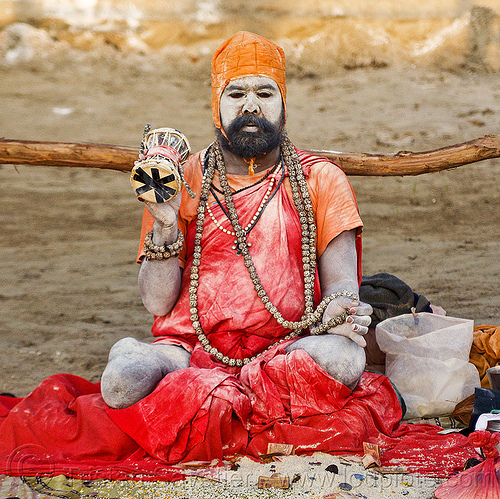 sadhu with skin covered of vibhuti sacred ash - kumbh mela 2013 (india), amputated leg, baba, bank notes, beard, coins, damaru drum, donations, hindu pilgrimage, hindu ritual drum, hinduism, holy ash, india, maha kumbh mela, man, money, necklaces, offering, paush purnima, pilgrim, red cloths, red color, rudraksha beads, sacred ash, sadhu, sitting, small drum, vibhuti, white ash, white skin