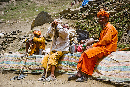 sadhus (hindu holy men) resting on trail - amarnath yatra (pilgrimage) - amarnath yatra (pilgrimage) - kashmir, amarnath yatra, babas, bhagwa, hiking canes, hindu holy men, hindu pilgrimage, hinduism, india, kashmir, man, mountain trail, mountains, pilgrims, resting, sadhus, saffron color, trekking, walking sticks