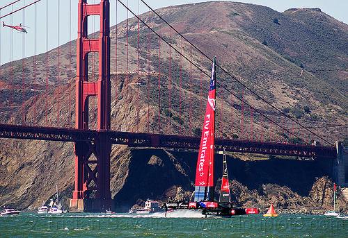 sailing hydrofoil catamaran emirates team new zealand near golden gate bridge - america's cup 2013 race (san francisco), ac72, advertising, america's cup, bay, boat, fast, foiling, helicopter, hydrofoil catamarans, hydrofoiling, hydrofoils, ocean, racing, sailboat, sailing hydrofoils, sea, ship, speed, sponsors, suspension bridge, water