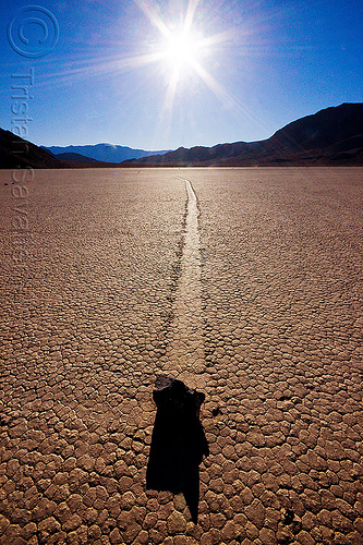 sailing rock on the racetrack - death valley, backlight, cracked mud, death valley, desert, dry lake, dry mud, mountains, moving rock, racetrack playa, sailing stone, sliding rock, sun, track