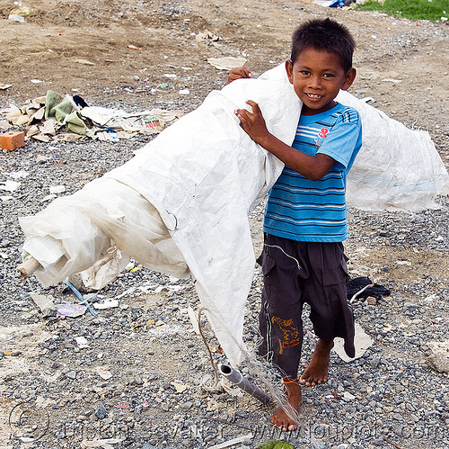 scavenger kig carrying white tarp, boy, child, garbage, homeless, homeless camp, kid, lahad datu, people, poor, roll, rubbish, trash