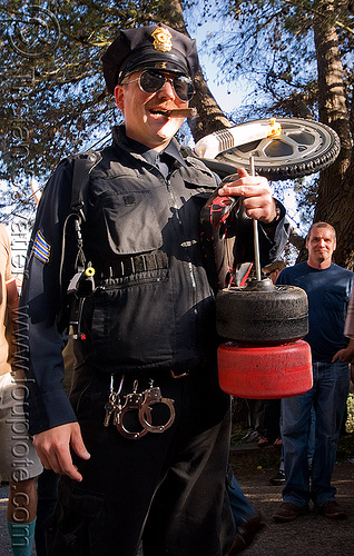 "SFPD police officer - BYOBW - ""bring your own big wheel"" race - toy tricycles (san francisco), big wheel, cigar smoking, drift trikes, handcuffs, law enforcement, police officer, potrero hill, race, sfpd, toy tricycle, toy trike, trike-drifting, uniform"