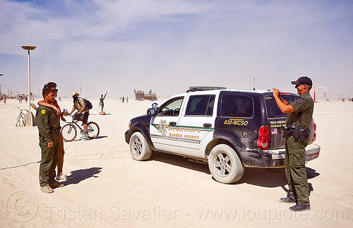 sheriff taking souvenir photo with naked man - burning man 2012, burning man, cops, jumpsuits, law enforcement, leo, officers, photographer, police uniform, sheriff, suv, tactical uniform, taking photo