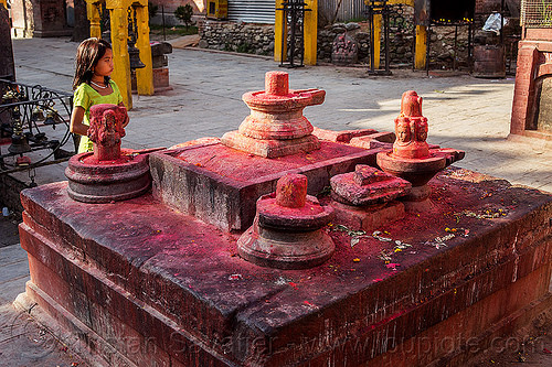 shiva lingas with red dye powder - budhanikantha temple (nepal), budhanikantha temple, child, dyes, girl, hindu temple, hinduism, kid, lingams, lingas, red, shiva lingam